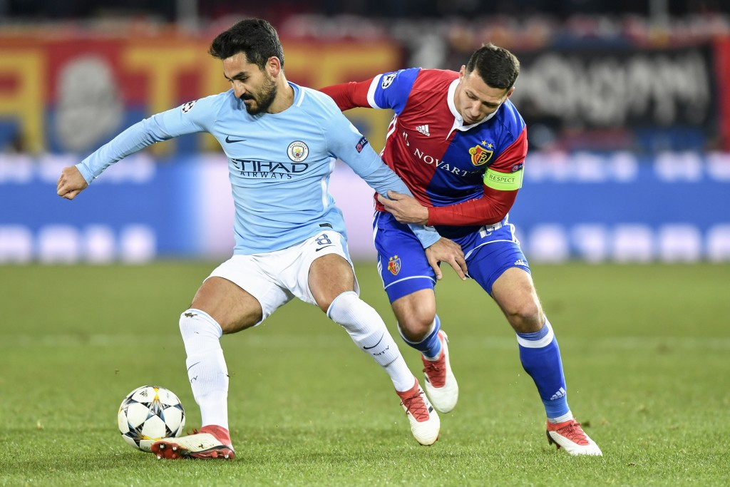 Manchester City's Ilkay Gundogan, left, fights for the ball against Basel's Marek Suchy, during the Champions League round of sixteen first leg soccer