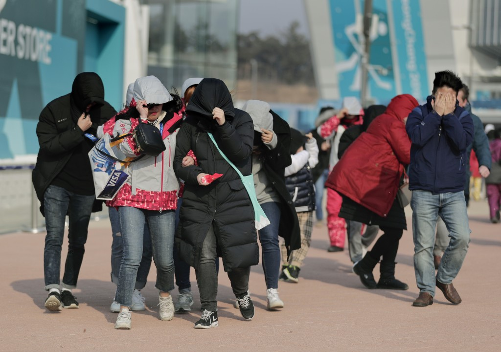 Visitors to Gangneung Olympic Park shield themselves from blowing dirt and debris from strong winds as they leave the park at the 2018 Winter Olympics