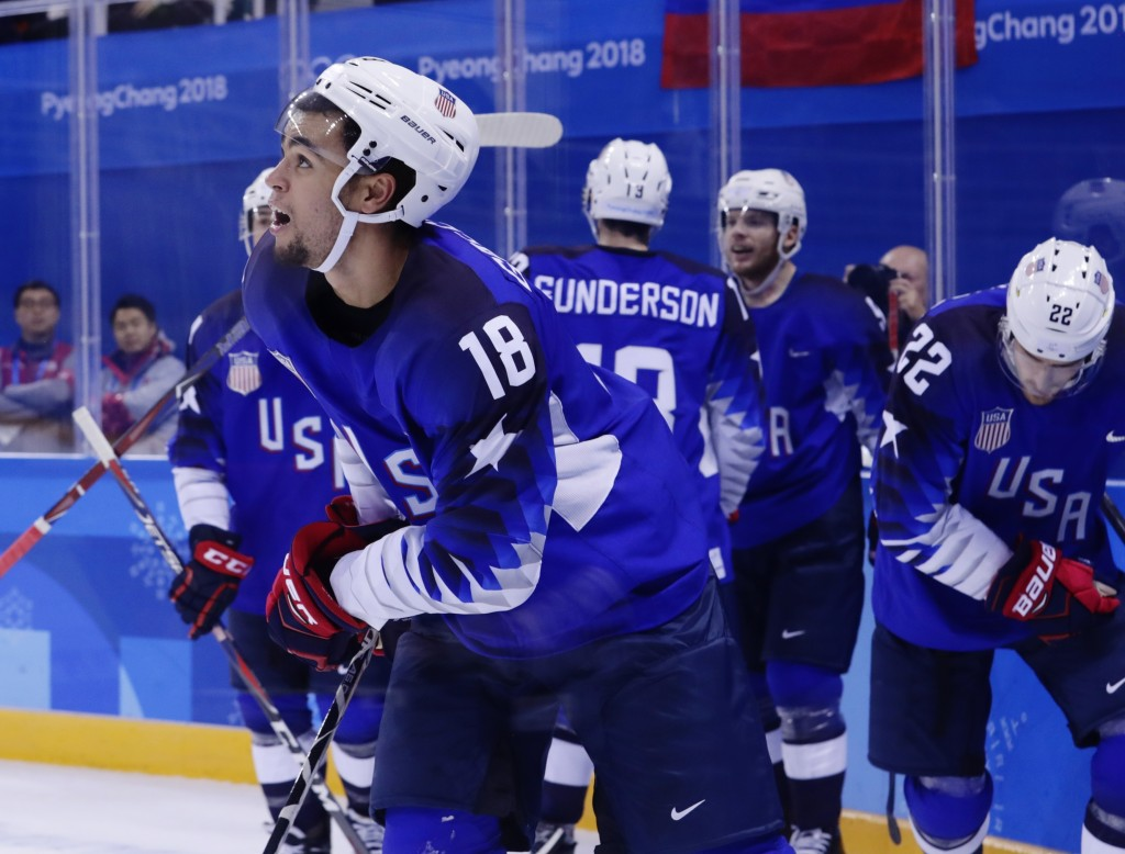 Jordan Greenway (18), of the United States, celebrates with teammates after scoring a goal against Slovenia during the second period of the preliminar