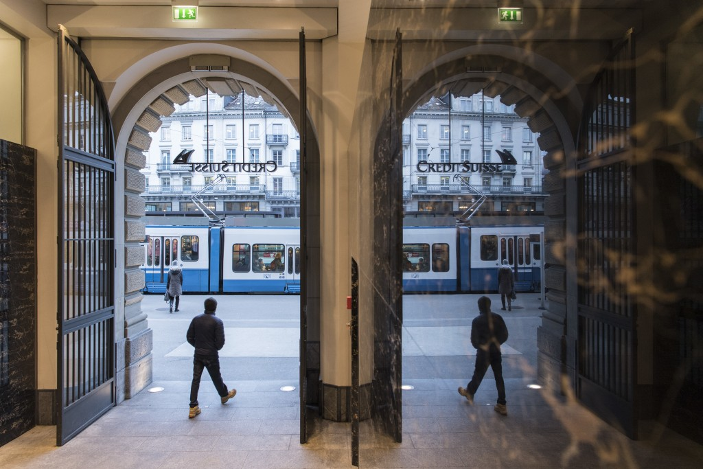 People walk in the front of the Credit Suisse bank at the tram stop Paradeplatz in the square's centre in Zurich, Switzerland, Wednesday, Feb. 14, 201