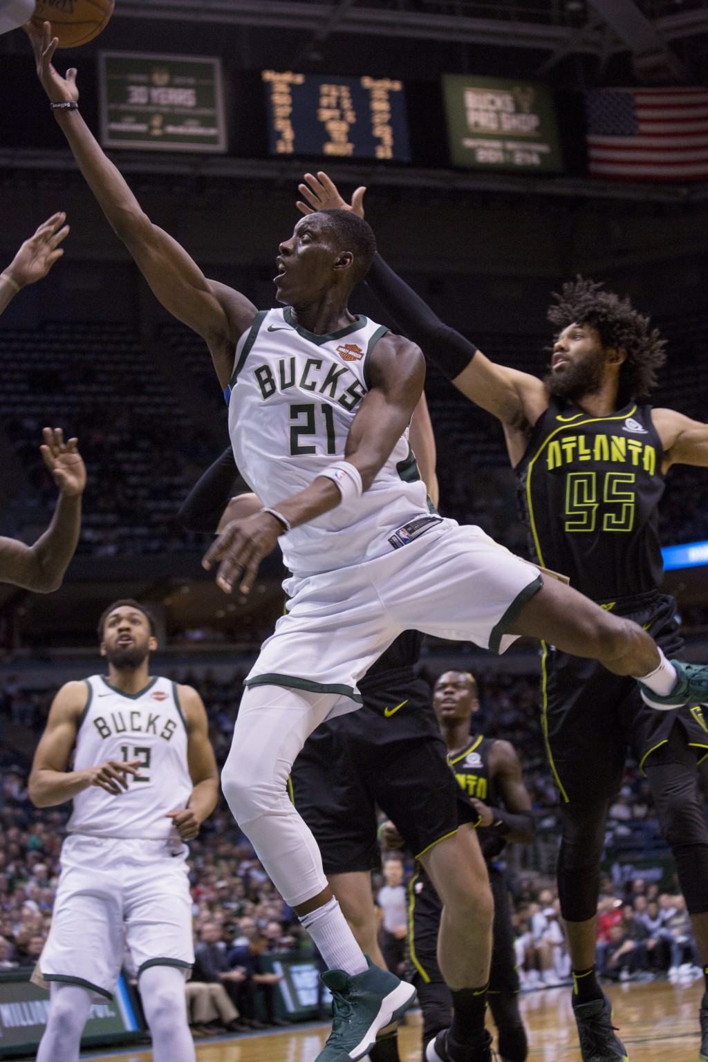 Milwaukee Bucks guard Tony Snell, center, goes up for a basket against the Atlanta Hawks during the first half of an NBA basketball game Tuesday, Feb.