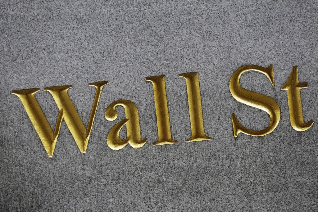 FILE - This July 6, 2015, file photo shows a sign for Wall Street carved into the side of a building in New York. The U.S. stock market opens at 9:30