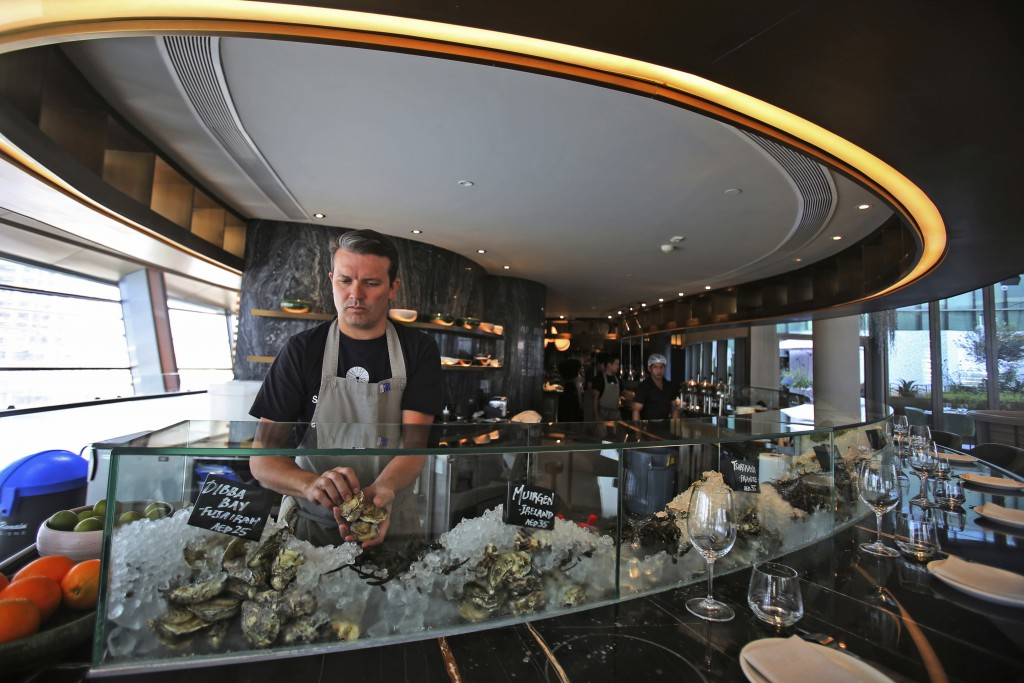 In this Jan. 24, 2018 photo, Carl Maunder, executive chef at the Maine Oyster Bar & Grill at Dubai Opera prepares an oyster dish, in Dubai, United Ara