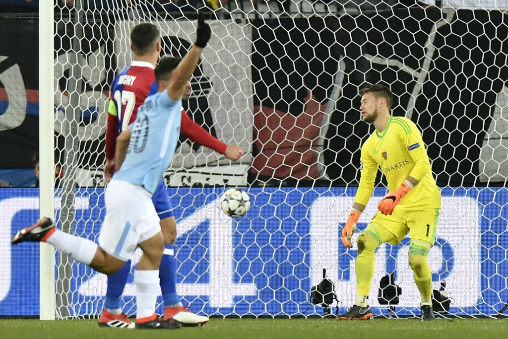 Manchester City's Sergio Aguero, front, celebrates his team's third goal, as Basel's Marek Suchy, left, and goalkeeper Tomas Vaclik watch, during the