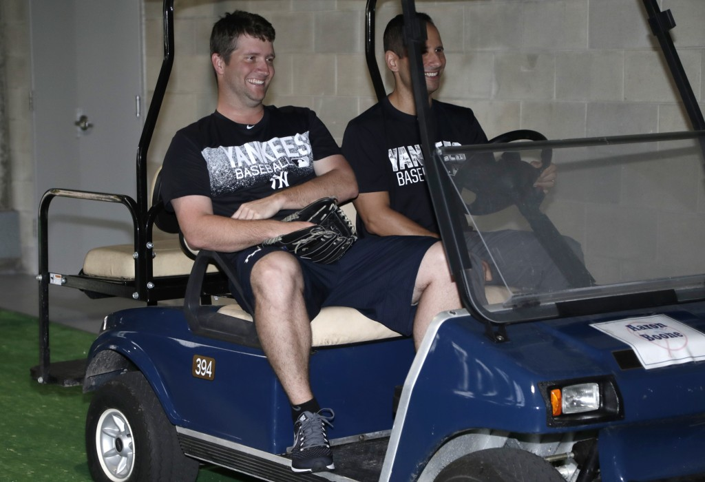 New York Yankees relief pitcher Adam Warren, left, rides in a golf cart at baseball spring training, Tuesday, Feb. 13, 2018, in Tampa, Fla. (AP Photo/