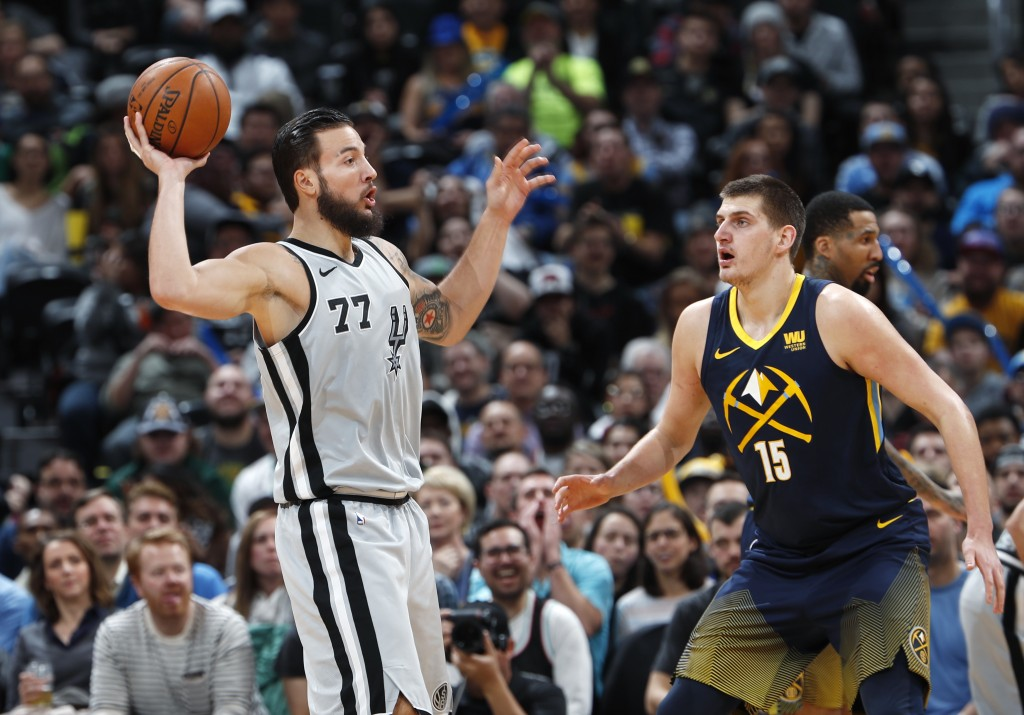 San Antonio Spurs center Joffrey Lauvergne, left, looks to pass the ball as Denver Nuggets center Nikola Jokic defends during the first half of an NBA