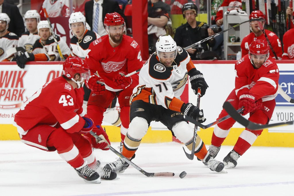 Anaheim Ducks' J.T. Brown (71) carries the puck against Detroit Red Wings' Darren Helm (43) and Frans Nielsen (51) in the first period of an NHL hocke