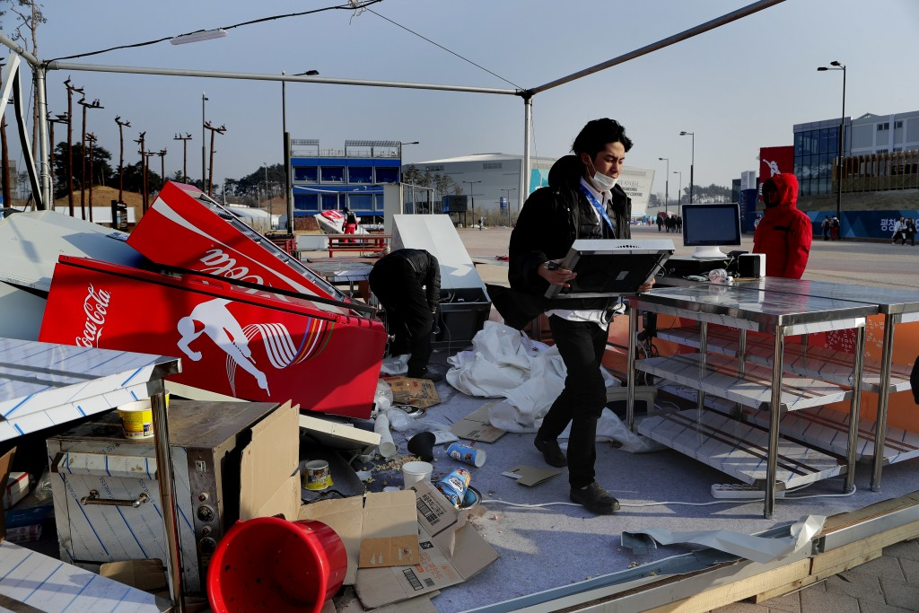 A concession stand worker carries away equipment after strong winds tore apart the food stand at Gangneung Olympic Park at the 2018 Winter Olympics in