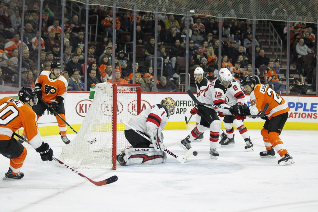 Philadelphia Flyers' Jori Lehtera, Scott Laughton, right, watches his shot head towards New Jersey Devils' Keith Kinkaid for a goal during the second
