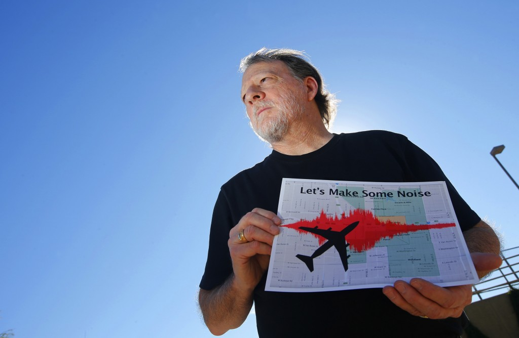 FILE - In this Feb. 6, 2015 file photo, Steve Dreiseszun, a resident of the F.Q. Story historic district in Phoenix, holds a graphic of the increased