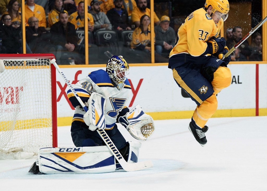 Nashville Predators left wing Viktor Arvidsson (33), of Sweden, takes a shot in the foot as he tries to leap out of the way in front of St. Louis Blue