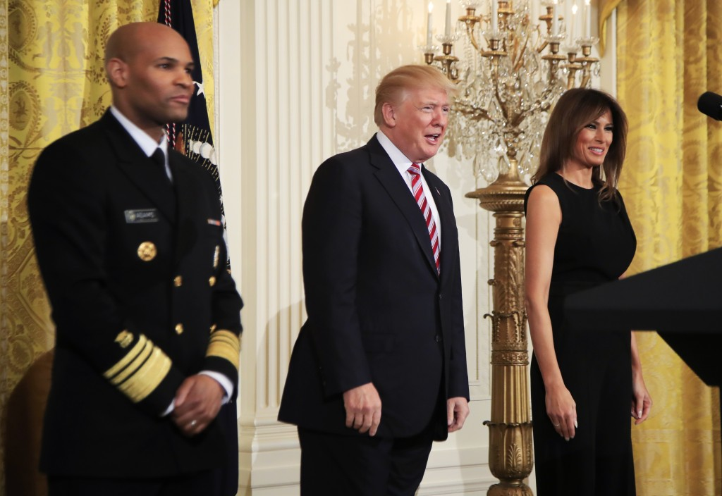 President Donald Trump, center with first lady Melania Trump and Surgeon General Jerome Adams, left, speaks during a National African American History