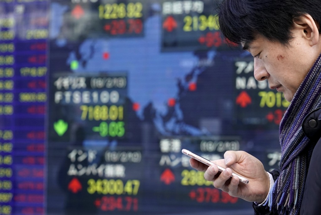 A man uses a smartphone in front of an electronic stock indicator of a securities firm in Tokyo, Wednesday, Feb. 14, 2018. Asian shares were mixed Wed