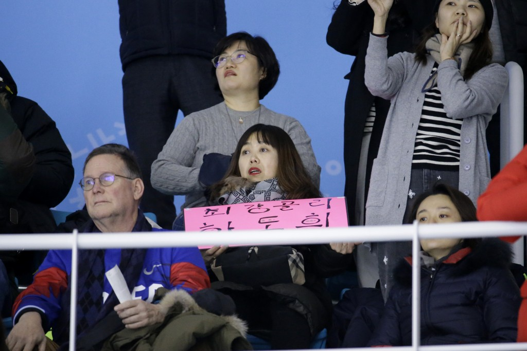 In a photo taken Monday, Feb. 12, 2018, Woo Hee-jun, center, mother of South Korean player Han Dohee, watches the Koreas play a women's hockey game ag
