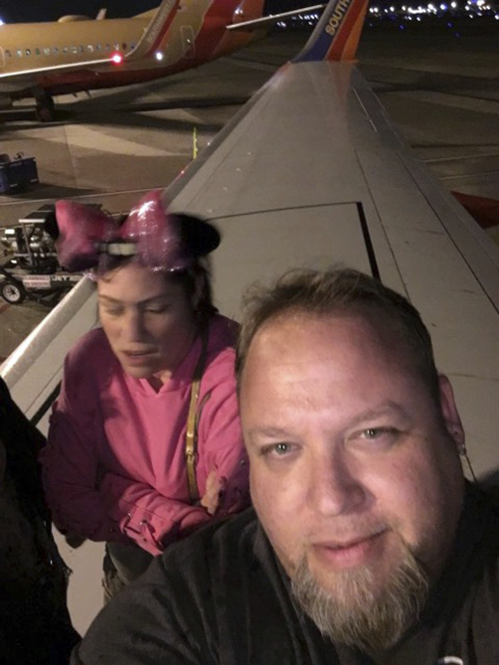 This Monday, Feb. 12, 2018 selfie by JC Arkham shows him and his wife Beth Vallacqua on the wing of a Southwest Airlines jet during their evacuation f