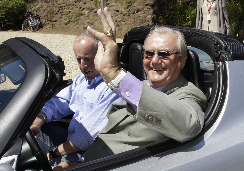 FILE - In this June 13, 2011, file photo, Denmark's Prince Henrik, right, waves as he drives a Tesla Roadster at the electric car maker's headquarters