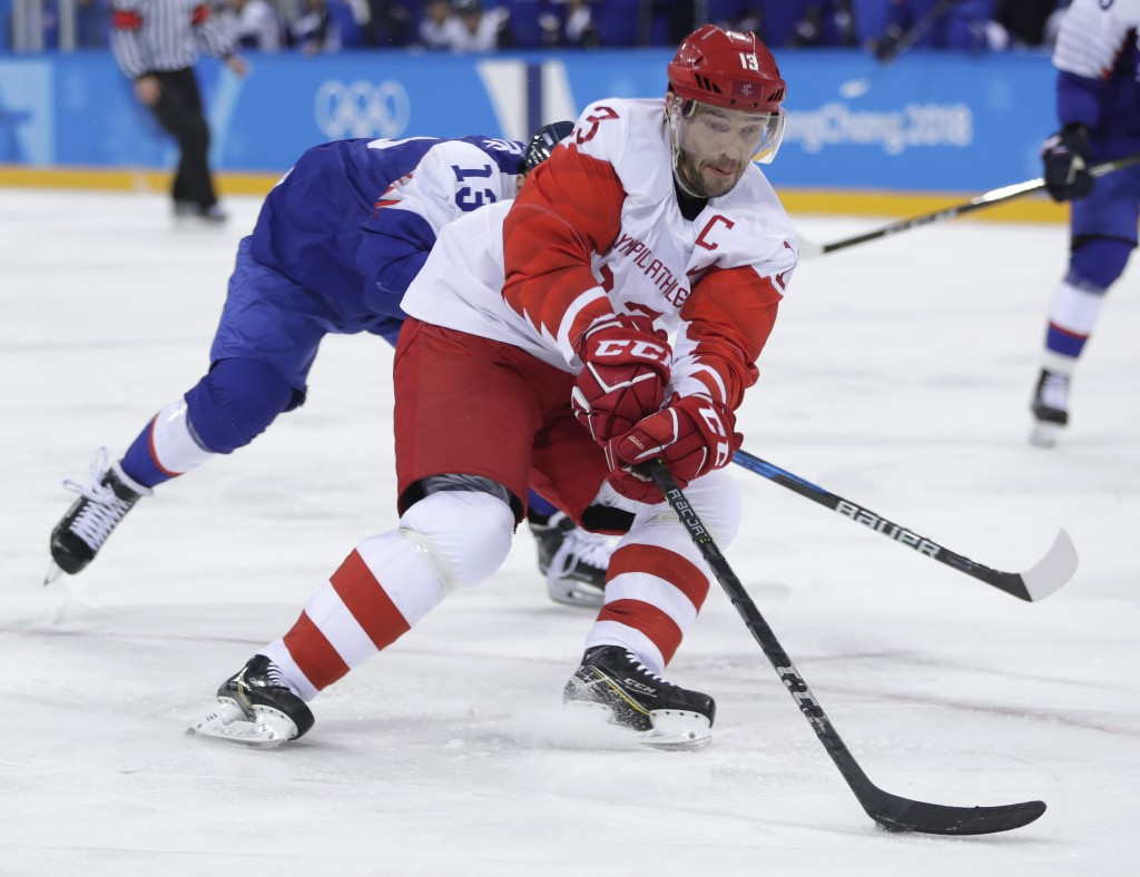 Russian athlete Pavel Datsyuk drives the puck against Michal Kristof, of Slovakia, during the second period of the preliminary round of the men's hock