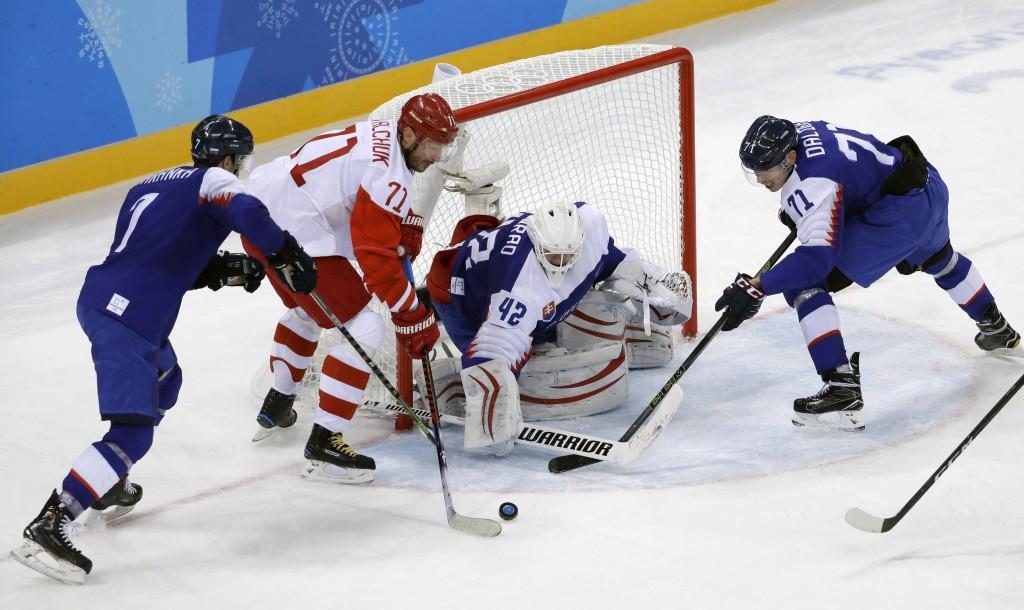 Russian athlete Ilya Kovalchuk (71) tries to shoots against Ivan Baranka (7) and Marek Daloga (71), of Slovakia, as Branislav Konrad (42) defends the