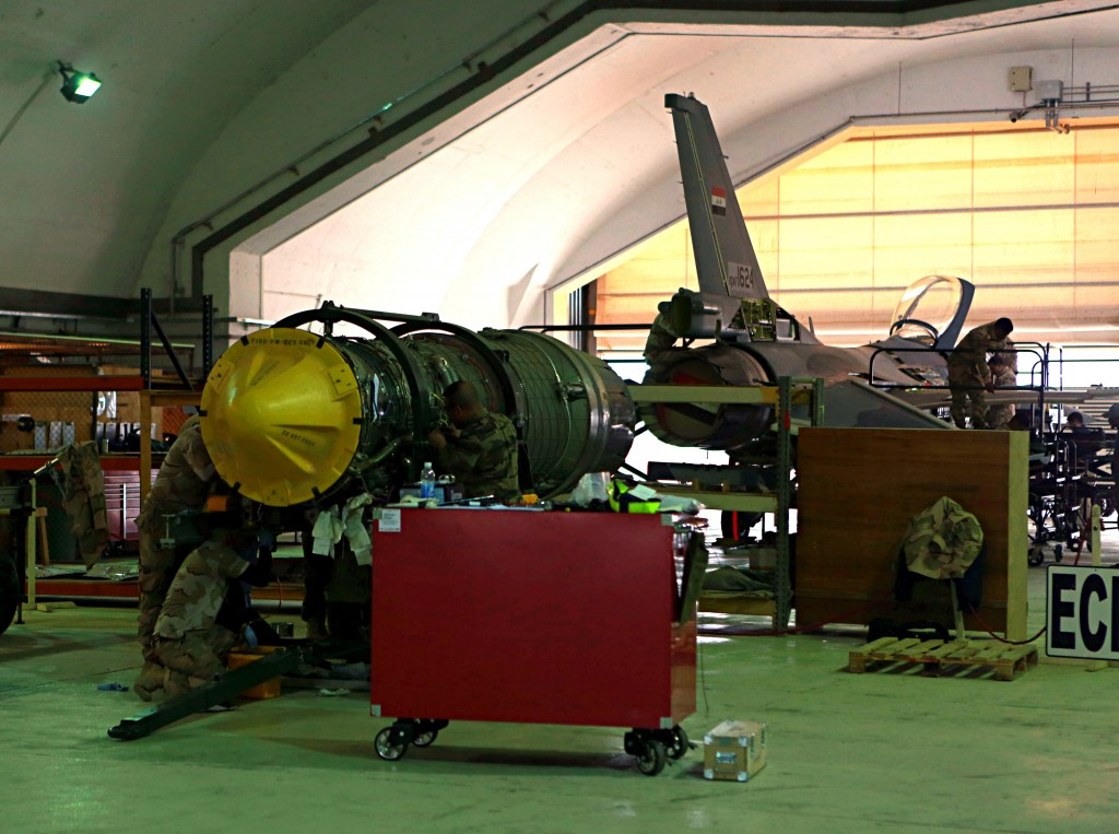 In this Tuesday, Feb. 13, 2018 photo, U.S. and Iraqi engineers do engine maintenance of a U.S.- made Iraqi Air Force F-16 fighter jet at the Balad Air