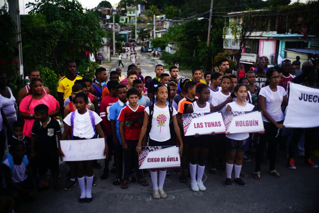 In this Jan. 22, 2018 photo, local children hold signs carrying the names of the provinces where young wrestlers, behind them, travelled from, as they