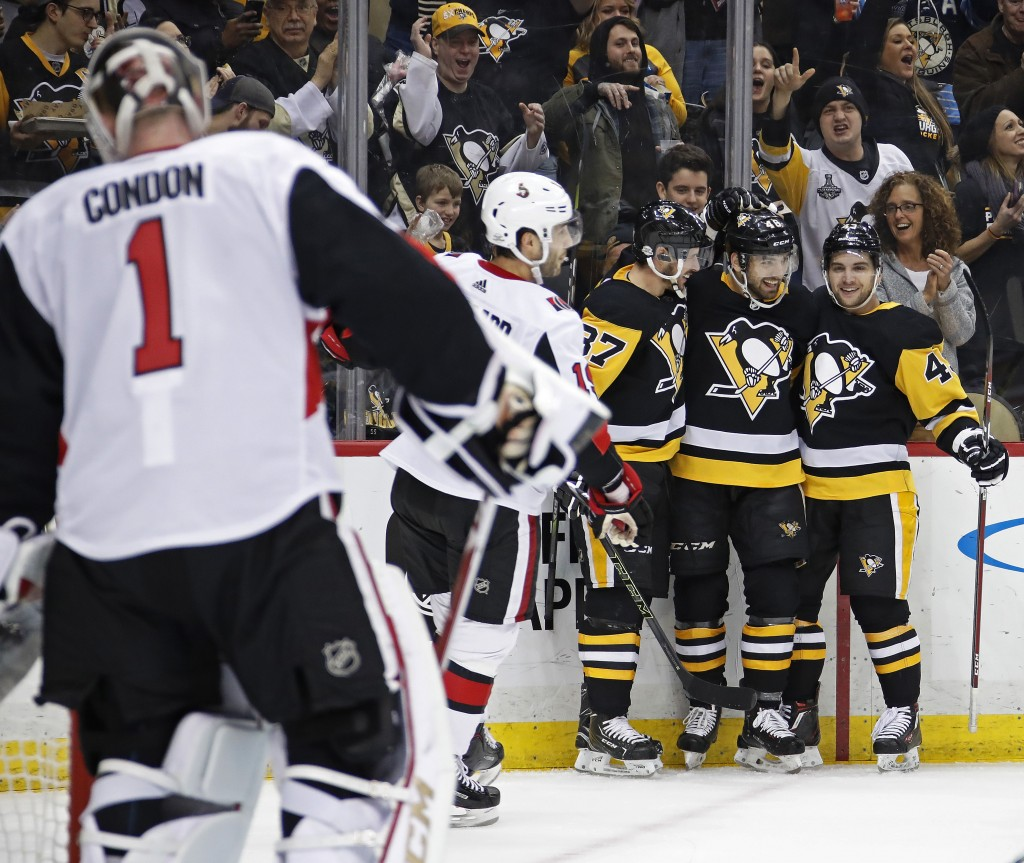 Pittsburgh Penguins' Zach Aston-Reese , second from right, celebrates his first NHL goal with Sidney Crosby (87) and Conor Sheary (43) as Ottawa Senat