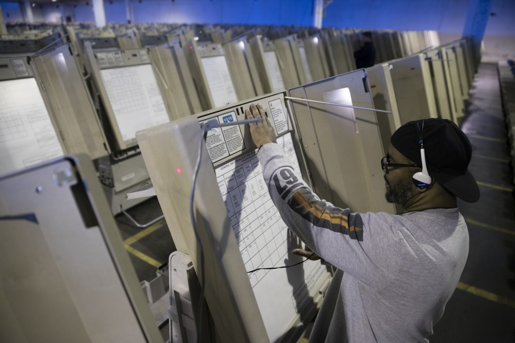 FILE- In this Oct. 14, 2016, file photo, a technician works to prepare voting machines to be used in the upcoming presidential election in Philadelphi