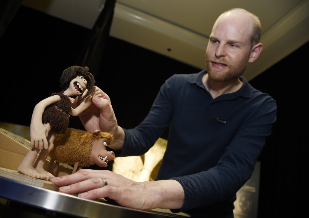 "In this Feb. 8, 2018 photo, Will Becher, an animation director for the stop-motion animated film ""Early Man,"" moves the arm of the puppet character Du"