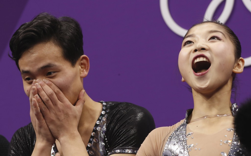 Ryom Tae Ok and Kim Ju Sik of North Korea react after their scores are posted following their performance in the pair figure skating short program in