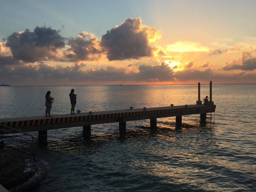 This Dec. 22, 2017 photo taken in Cozumel, Mexico shows people on a pier at sunset over the Caribbean. Mexico is a popular vacation destination for wi