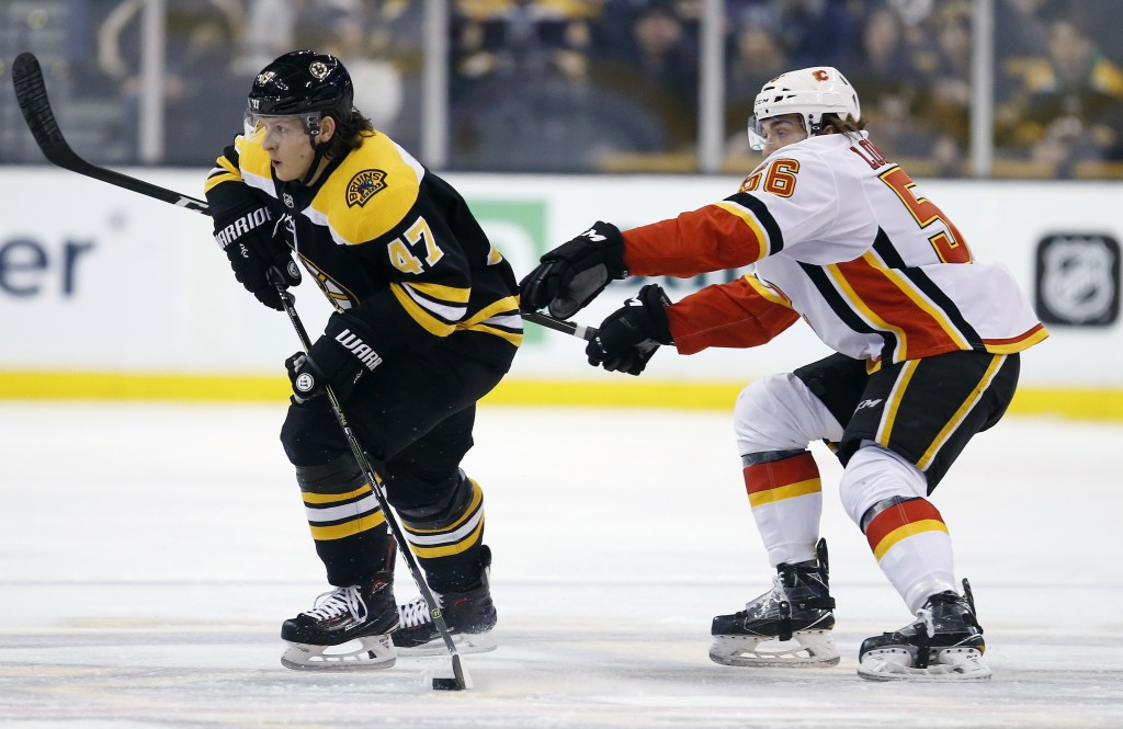 Calgary Flames' Ryan Lomberg (56) battles Boston Bruins' Torey Krug (47) for the puck during the first period of an NHL hockey game in Boston, Tuesday