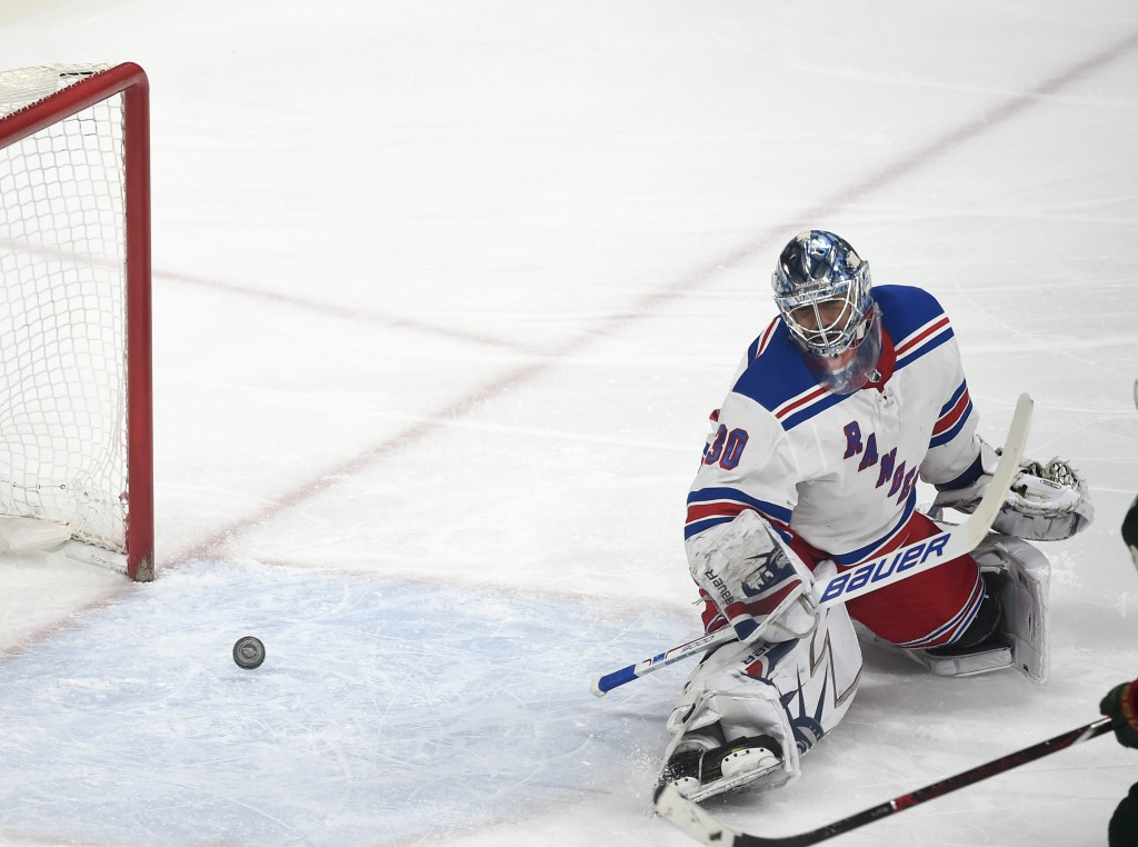 New York Rangers goalie Henrik Lundqvist, of Sweden, gives up a goal to Minnesota Wild center Eric Staal during the first period of an NHL hockey game