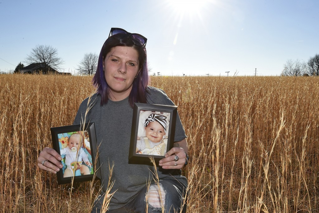 Sarah Sherbert poses for a photo in Anderson, S.C., on Monday, Feb. 5, 2018, holding photos of her children when they were infants. The two babies, bo