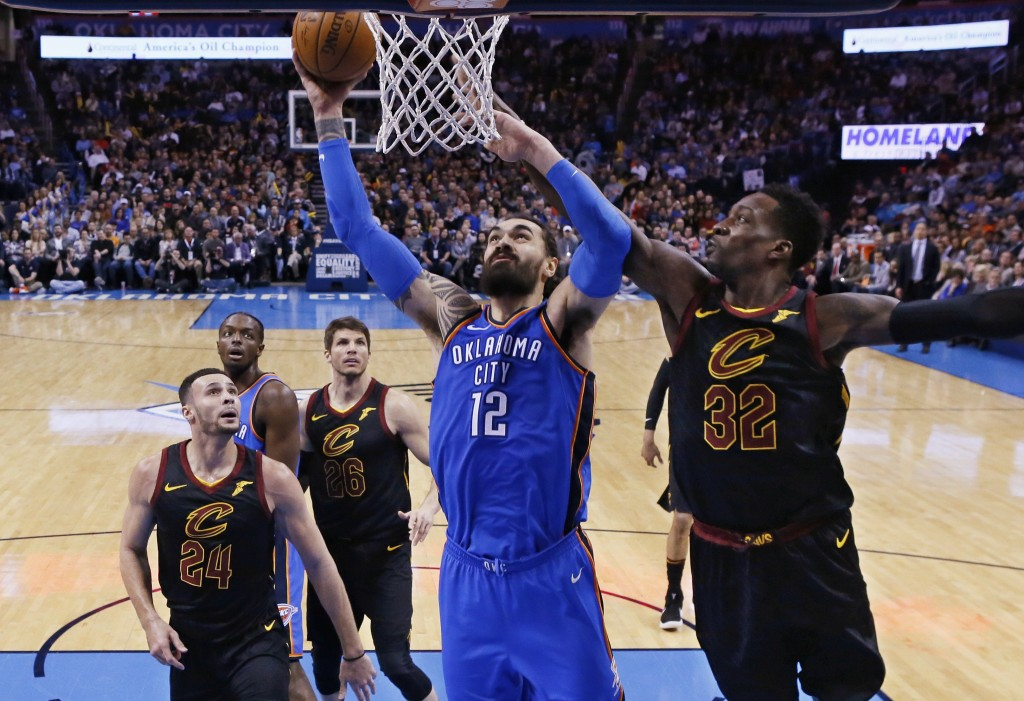 Oklahoma City Thunder center Steven Adams (12) shoots between Cleveland Cavaliers forward Larry Nance Jr. (24) and forward Jeff Green (32) during the