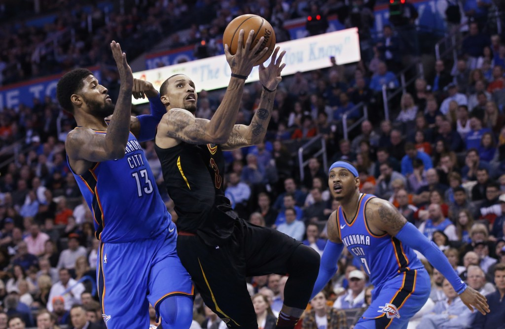 Cleveland Cavaliers guard George Hill (3) shoots between Oklahoma City Thunder forward Paul George (13) and forward Carmelo Anthony (7) during the fir