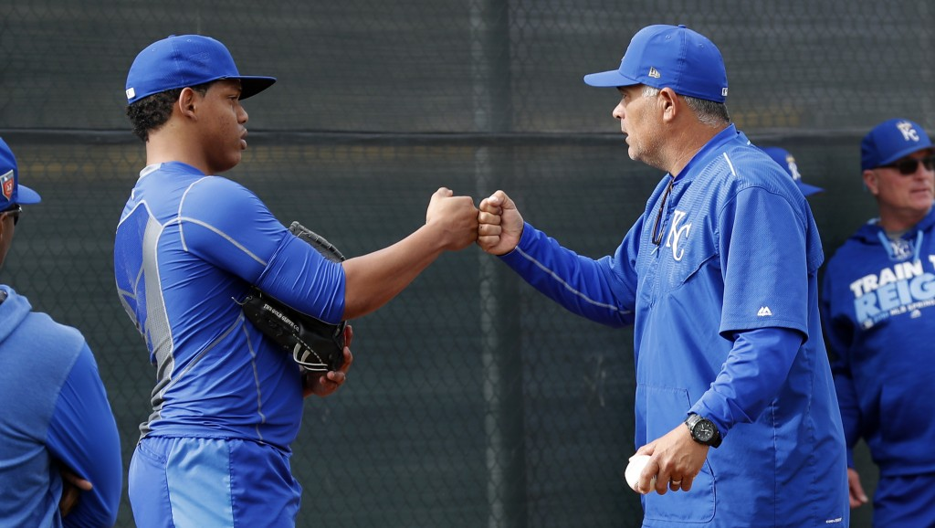 Pitcher Gustavo Tejeda, left, fist bumps with rehab pitching coach Carlos Reyes, right, during a Kansas City Royals baseball spring training workout,