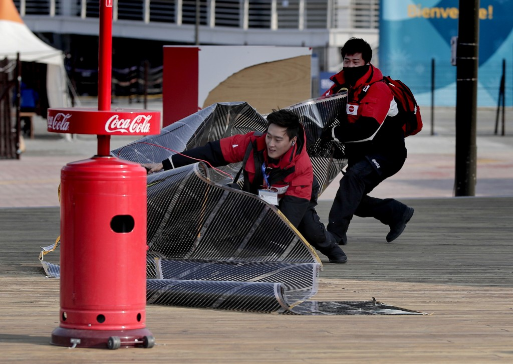 A vendor chases down solar film that blew off the top of the Coca-Cola building inside Gangneung Olympic Park at the 2018 Winter Olympics in Gangneung