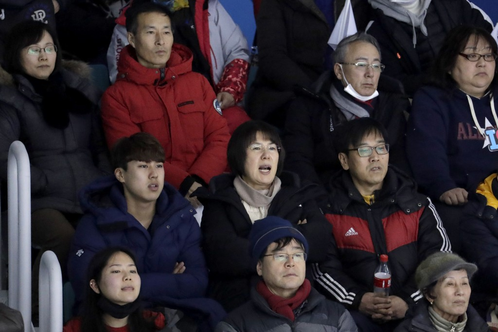 In a photo taken Monday, Feb. 12, 2018, Heo Saeng-gum, center, mother of South Korean player Kim Selin, reacts while sitting with her son Kim Se Hyung