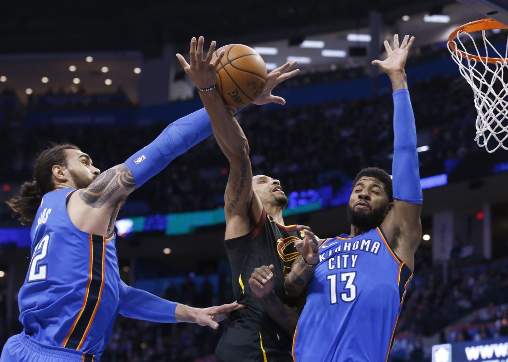 Oklahoma City Thunder center Steven Adams, left, knocks the ball away from Cleveland Cavaliers guard George Hill, center, as Hill shoots in front of f