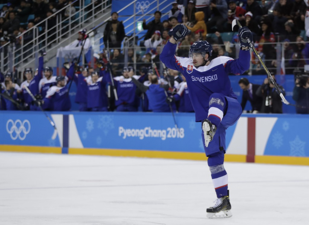 Peter Ceresnak (14), of Slovakia, reacts after scoring a goal against the team from Russia during the third period of the preliminary round of the men