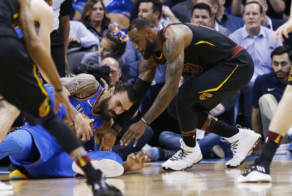 Cleveland Cavaliers forward LeBron James, right, reaches in for the ball held by Oklahoma City Thunder center Steven Adams during the first half of an