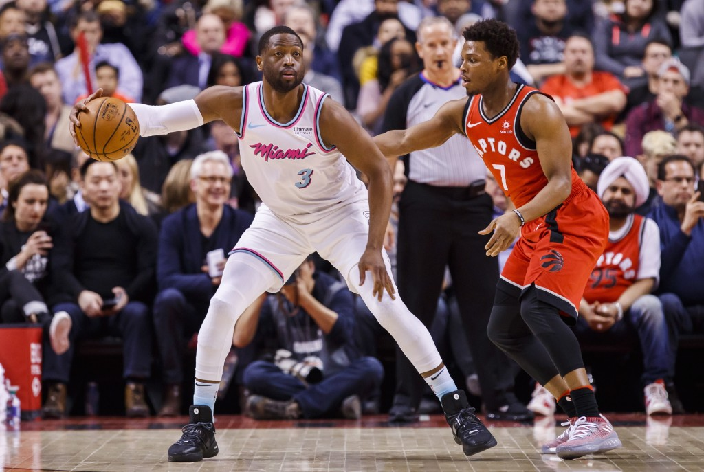 Miami Heat guard Dwyane Wade is guarded by Toronto Raptors' guard Kyle Lowry, right, during the first half of an NBA basketball game, Tuesday, Feb. 13
