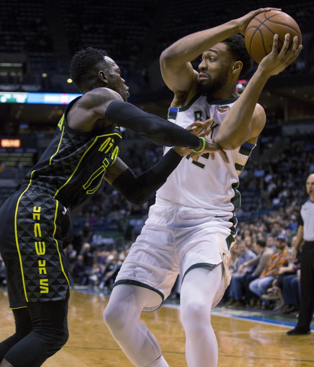 Milwaukee Bucks forward Jabari Parker, right, is defended by Atlanta Hawks guard Dennis Schroder, left, during the first half of an NBA basketball gam