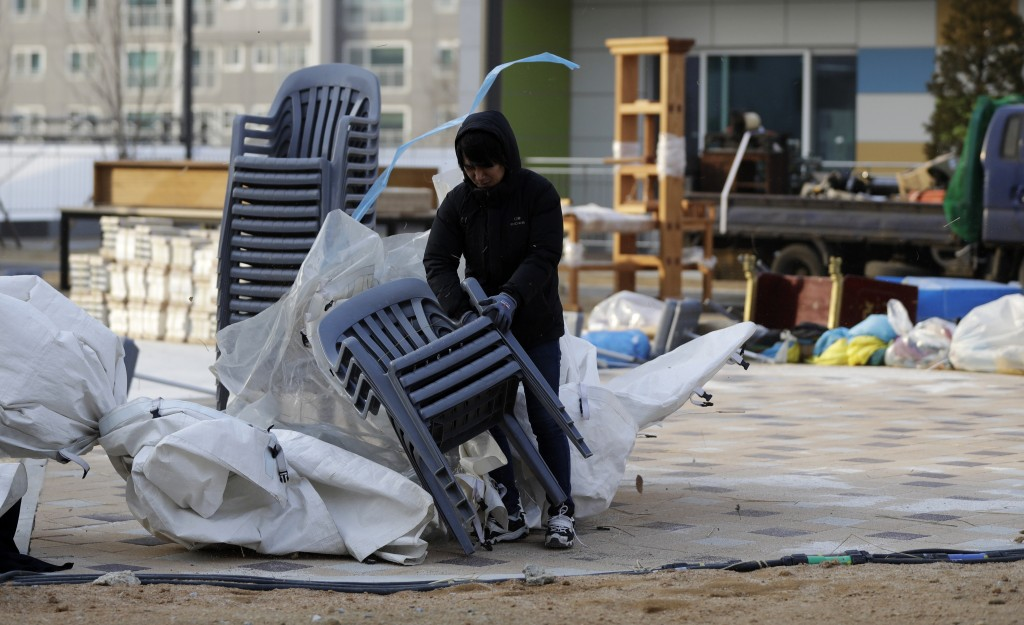 A volunteer gathers plastic chairs blown over by fierce wind at the Gangneung Media Village in Gangneung, South Korea, Wednesday, Feb. 14, 2018. (AP P