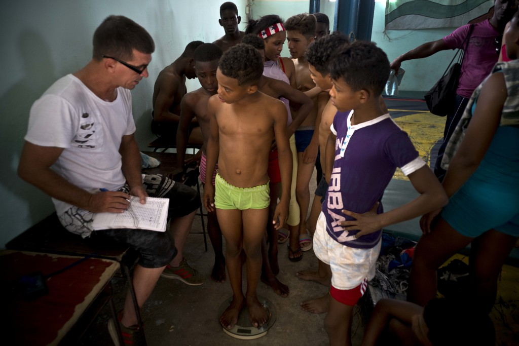 """In this Jan. 22, 2018 photo, young wrestlers are weighed by an instructor during the week-long student wrestling championship coined """"The truth of my"""