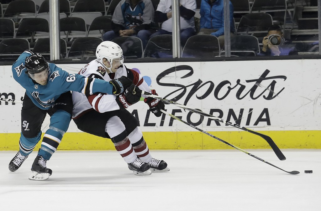 San Jose Sharks defenseman Justin Braun, left, and right wing Josh Archibald (45) reach for the puck during the first period of an NHL hockey game in
