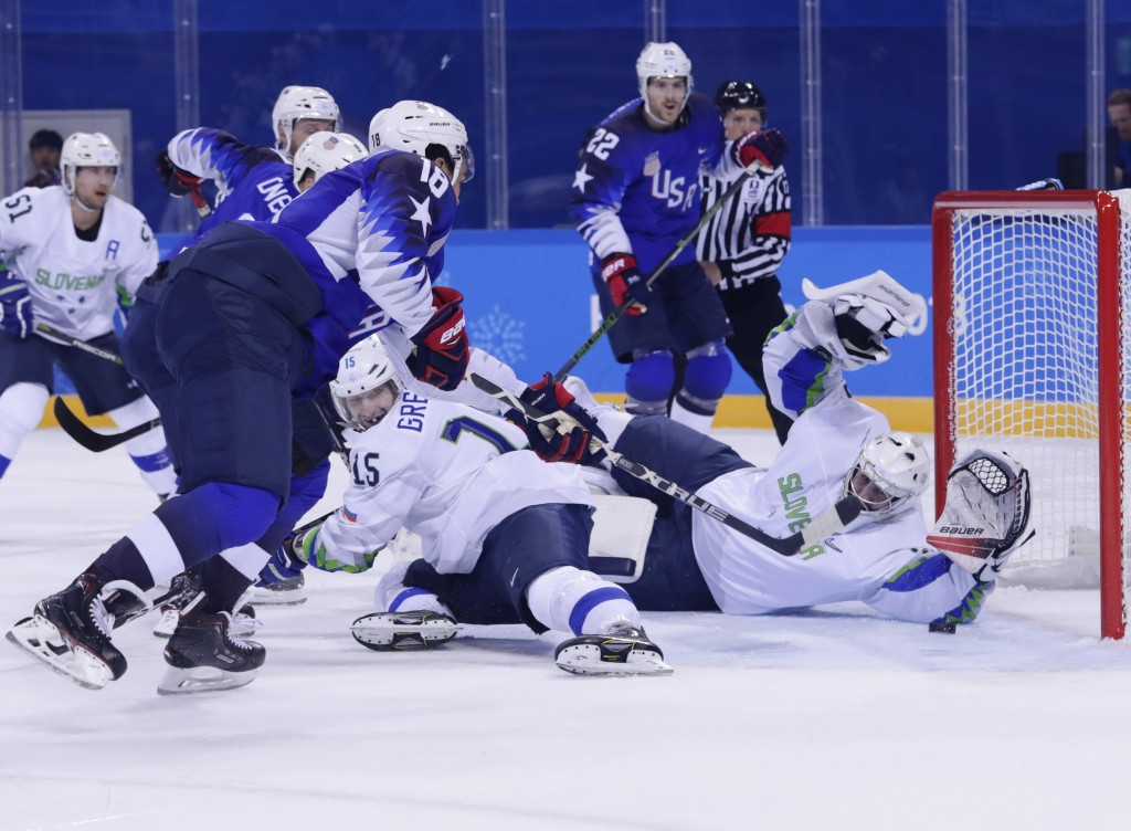 Jordan Greenway (18), of the United States, shoots the puck past goaltender Gasper Kroselj (32), of Slovenia, for a goal during the second period of t