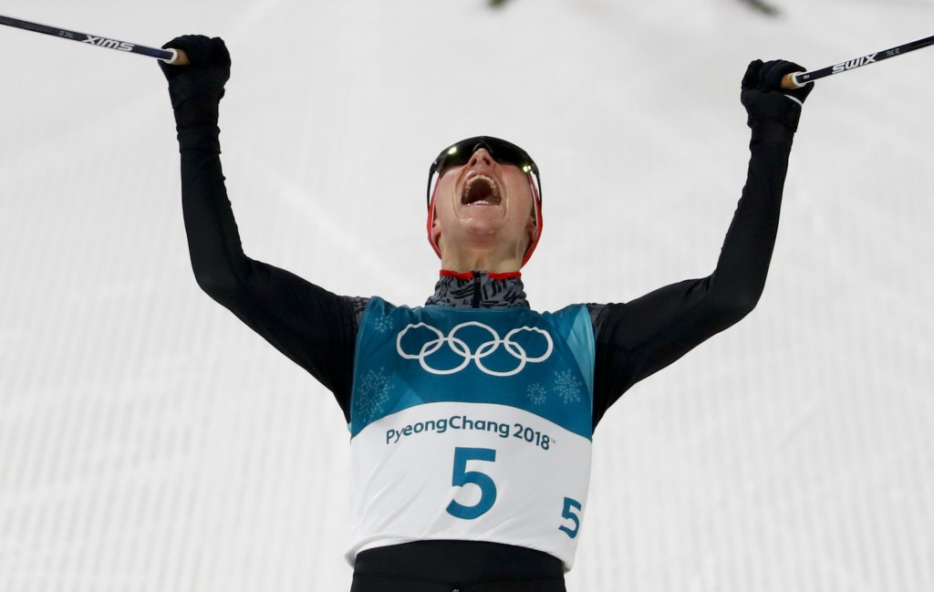 Eric Frenzel, of Germany, celebrates after winning the the gold medal after the 10km cross-country skiing portion of the nordic combined event at the