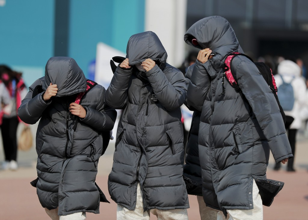 Volunteer workers at Gangneung Olympic Park shield themselves from blowing dirt and debris from strong winds as they leave the park at the 2018 Winter