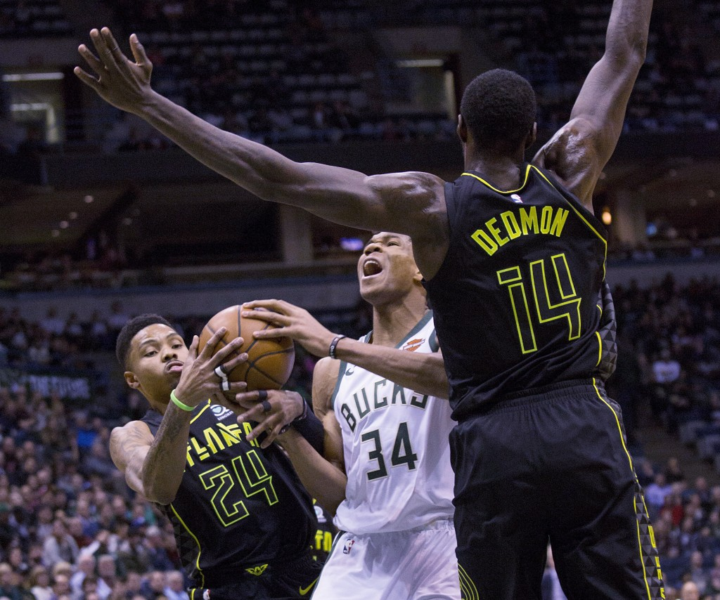 Milwaukee Bucks forward Giannis Antetokounmpo, center, is defended by Atlanta Hawks guard Kent Bazemore, left, and Dewayne Dedmon, right, during the f