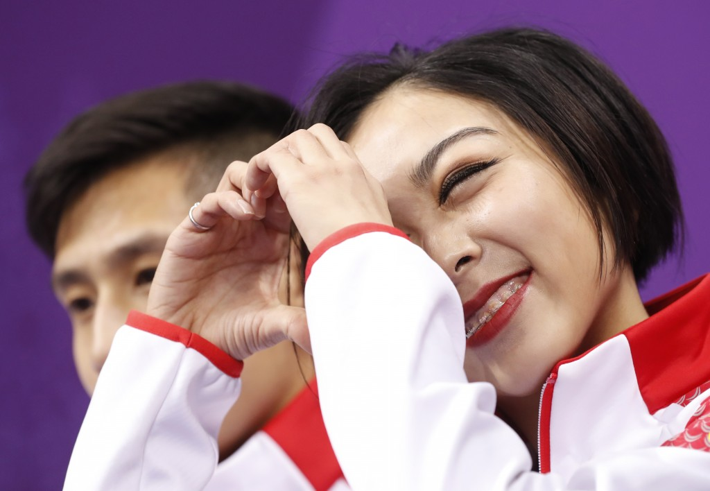 Sui Wenjing and Han Cong of China react as they wait for their scores following their performance in the pair figure skating short program in the Gang